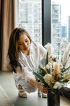 woman crouches to arrange flowers in a vase