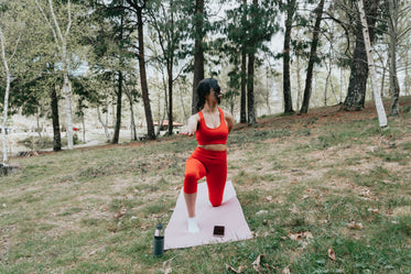 woman does yoga on a pink yoga mat outdoors