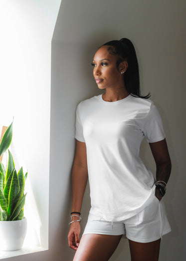 woman dressed in white leans against a wall