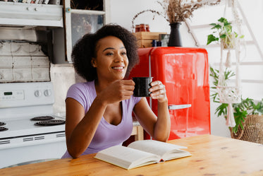 woman enjoying coffee and book in the kitchen