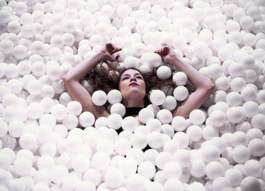 woman floating with arms raised in ball pit