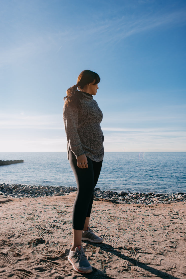 Woman Glances Back At The Sea Behind Her In The Morning Light