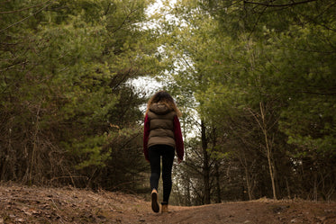woman hikes through forest clearing
