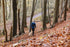 woman hiking with dog in fall leaves