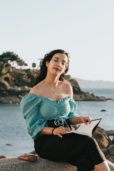 woman holds a book and sits on rocks by the water