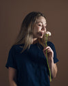 woman holds and smells a single ranunculus flower