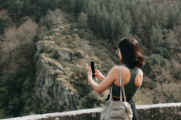 woman holds her cellphone out to take a picture outdoors