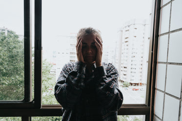 woman holds her hands to her facein front of a window