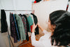woman holds her phone out to take a picture of clothing