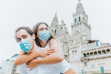 woman hugs man from behind while wearing blue facemask