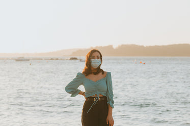 woman in a facemask stands in front of large lake