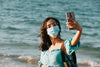 woman in a facemask takes a selfie with her phone