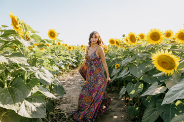 woman in a floral dress stands in a sunflower field