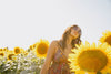 woman in a floral dress surrounded by sunflowers