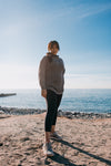 woman in a sweater stands on a beach in the morning
