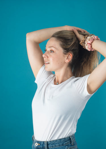 woman in a white shirt puts her hair up with scrunchies