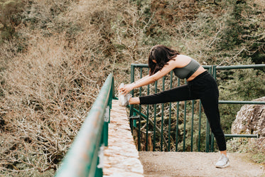 woman in active wear stretches her leg outdoors