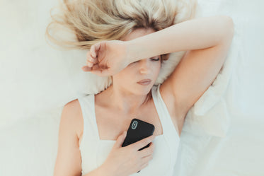 woman in bed on her cellphone with one arm up
