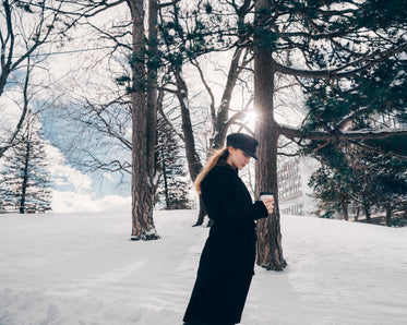 woman in black trench in winter woods