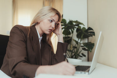 woman in brown suit sits and looks at her laptop screen