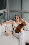 woman in cateye sunglasses sits with a puppy