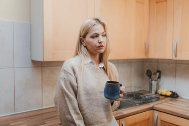 woman in collared shirt in the kitchen holding a mug