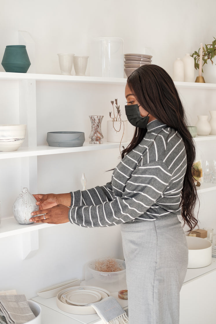 Woman In Face Mask Picks Up A Product