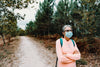 woman in face mask stands on a hiking trail