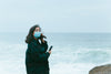 woman in face masks stands in front of ocean view