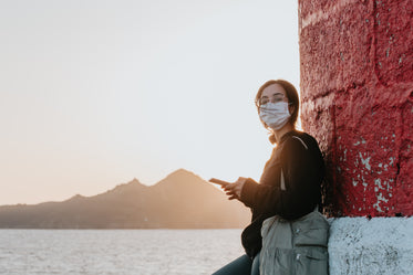 woman in facemask leans against a wall by water