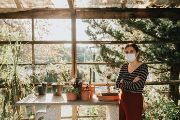 woman in facemask next to potted plants on table