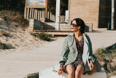 woman in floral dress sits by a wooden boardwalk