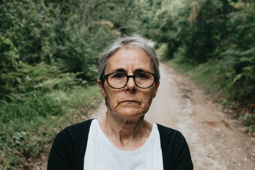 woman in glasses looks at the camera with a trail behind her