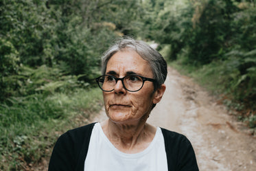 woman in glasses looks left on a green lined dirt trail