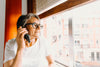 woman in glasses on the phone while looking out a window