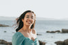 woman in glasses smiles by the rocky shoreline