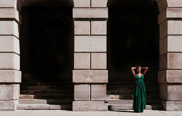 woman in green dress standing in front of archway