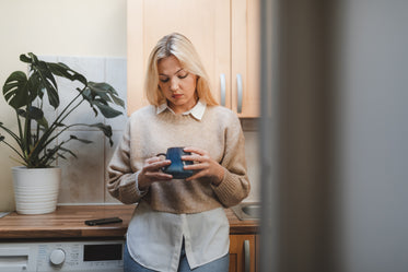woman in her kitchen looks into her mug