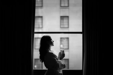 woman in hotel room window with coffee