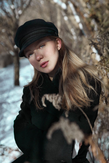 woman in newsboy cap in woods
