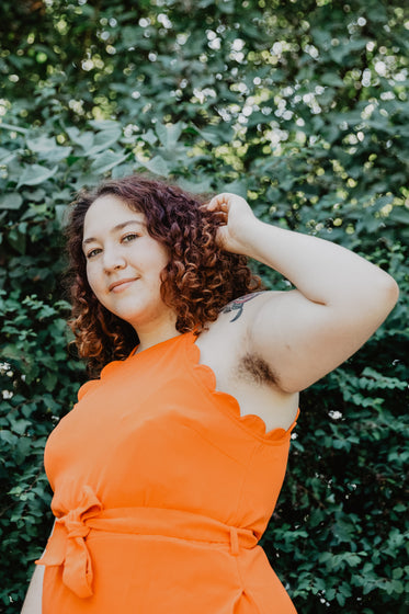 woman in orange top by green plant