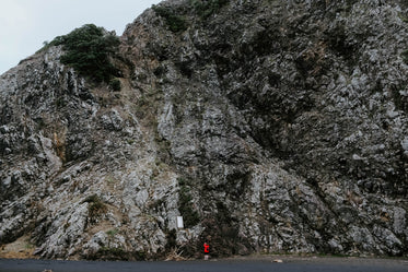 woman in red at foot of cliff