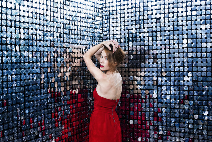 Woman In Red Dress Rests Elbows Against Wall Of Mirrors
