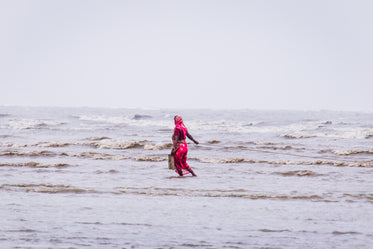 woman in red walking through shallow water