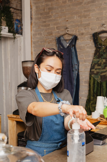 woman in retail store sanitizing her hands