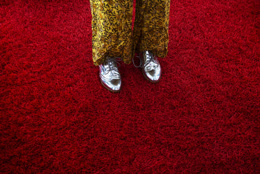 woman in silver oxfords crossing red shag carpet
