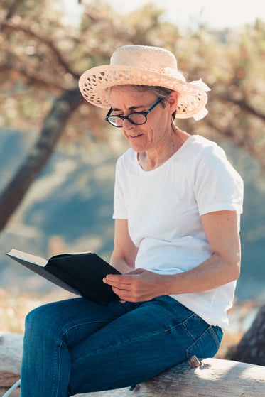 woman in straw hat on a wooden log reading a book