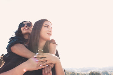 woman in sunglasses hugs the woman in front of her
