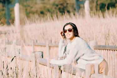 woman in sunglasses leans on a wooden fence