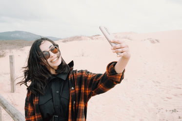 woman in sunglasses takes a selfie at the beach